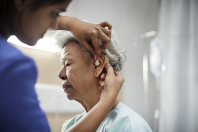 caregiver assisting senior woman for her hearing aid