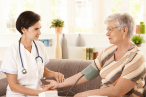 nurse checking blood pressure of senior woman