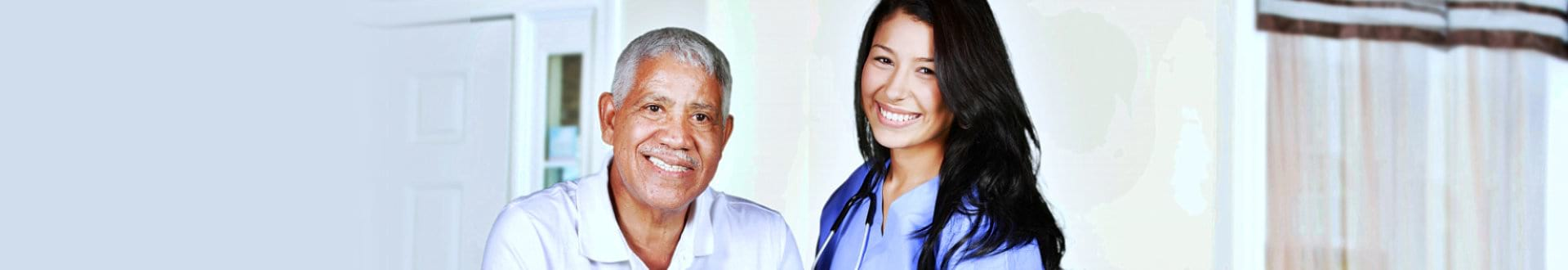 senior man with female caregiver smiling
