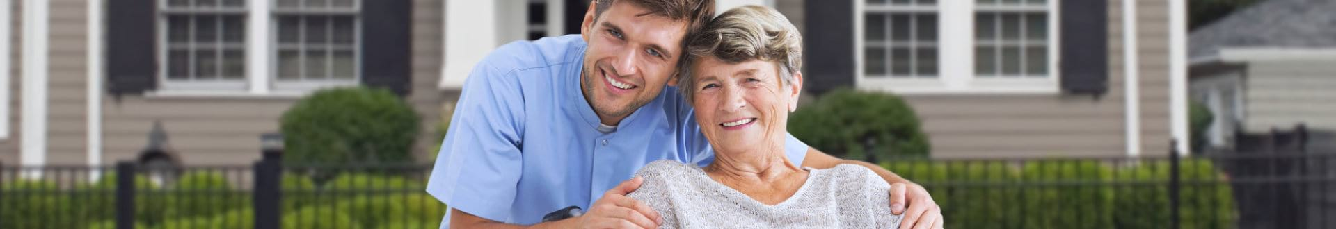 male caregiver with senior woman on wheelchair smiling